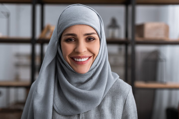 Keuken foto achterwand Honden smiling muslim woman in hijab looking at camera in living room, domestic violence concept