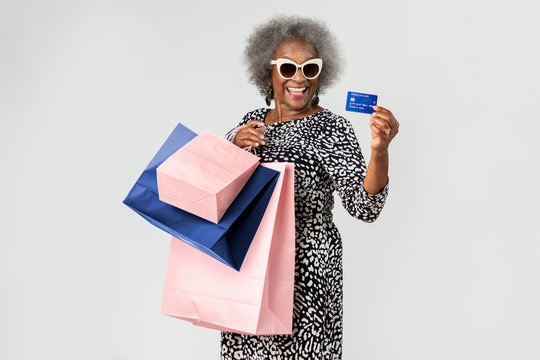 Cheerful senior woman on a shopping spree with a credit card