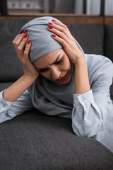 Keuken foto achterwand Texturen depressed muslim woman touching hijab and crying in living room, domestic violence concept