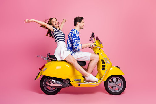 Profile side view portrait of his he her she nice attractive carefree cheerful cheery couple riding moped spending weekend vacation journey having fun isolated on pink pastel color background