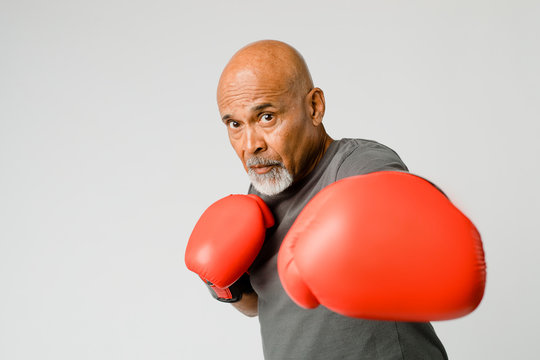 Senior man with red boxing gloves