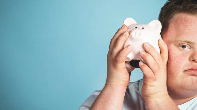 Young man with Down syndrome checking his piggy bank