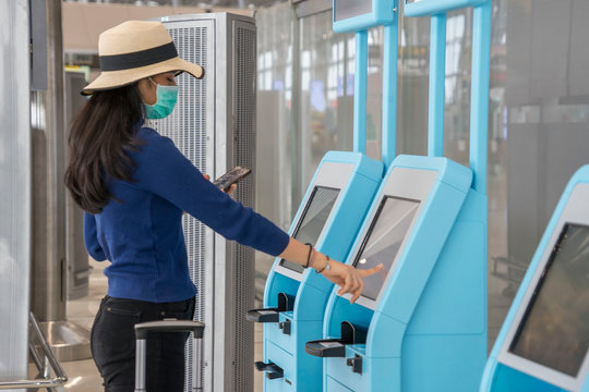 Backpacker travelers Asian women wearing masks covid19 disease Prevention and Check-in, ticket issuing, boarding pass, automatic at the airport terminal.New normal and travel concept.