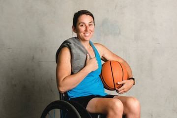 Happy female athlete in a wheelchair with a basketball