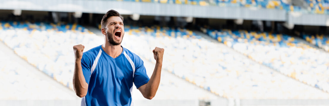 emotional professional soccer player in blue and white uniform showing yes gesture at stadium, panoramic shot