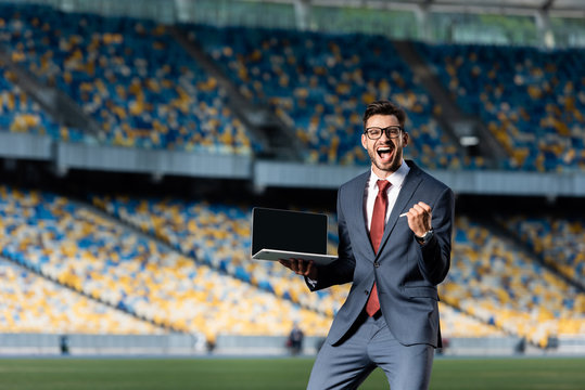 happy young businessman in suit holding laptop with blank screen and showing yes gesture at stadium
