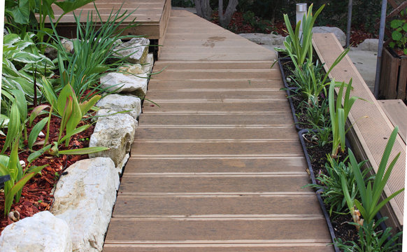Design of a modern garden. Walkways made of wood-plastic composite boards. A border made of natural stone and flower pots. Gardening and decoration of the house plot. Solar lights.