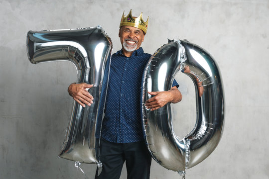 Cheerful senior man holding silver balloons for his 70th birthday celebration
