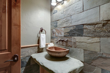 Absolutly stunning bathroom interior deisgn in a luxury rustic cabin style American home with stone and wood, venetian plaster and caling tones on nature.
