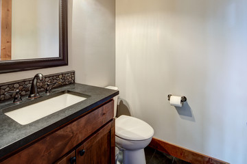 New rustic luxury home bathroom for guest design details with rich wood and grey stone with natural tiles on the floor.