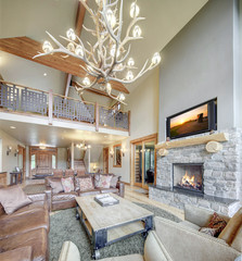 Amazing grand new luxury home with soft natural wall color and light hardwood floor, two story tall living room with sky bridge and leather furniture.