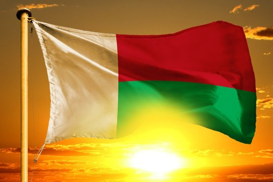 Madagascar flag weaving on the beautiful orange sunset with clouds background