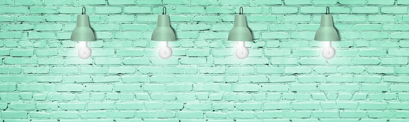 Mint green painted brick wall with lamps. Modern interior decorative lighting