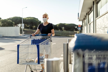 Woman wearing protective face mask with shopping cart