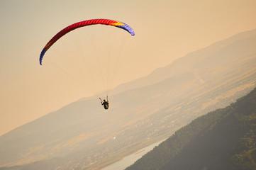 Paralotniarz leci na paralotni, w tle piękny krajobraz i pomarańcz zachodzącego słońca