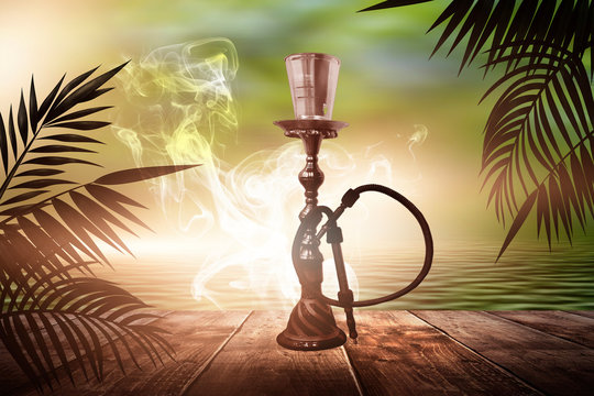 Oriental hookah with smoke on a background of a sea evening landscape with sunset. Palm tree branches, silhouettes, sunlight. Hookah on a wooden table. Night view, open-air seascape.