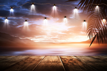 Fototapeten Schokobraun Hanging night lanterns on the pier, against the backdrop of a sea evening landscape with sunset. Palm tree branches, silhouettes, sunlight. Wooden table. Night view, open-air seascape.