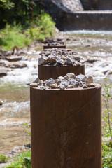 Eisensäulen mit Steinen befühlt als Treibholzsperre im Wasserlauf  im Jenbach bei Bad Feilnbach
