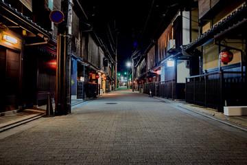 Fotomurales - Empty Road Along Buildings At Night
