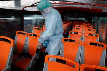 A staff wears a full body protective suit while disinfecting a Taipei Sightseeing bus before the bus head out on the designated route to various tourist sites across the city in Taipei,