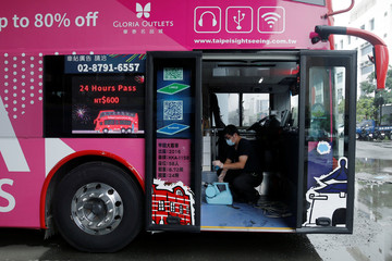 A staff member collects equipments after disinfecting a Taipei Sightseeing bus before the bus head out on the designated route to various tourist sites across the city in Taipei,