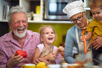 Happy grandparents with grandchildren making breakfast in kitchen.