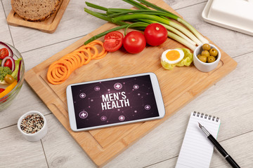 MEN'S HEALTH concept in tablet pc with healthy food around, top view