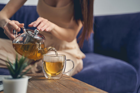 Young woman pouring herbal tea into glass cup