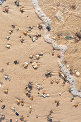 Shore Detail - Objects at Natural Beach / Beach sand top view background with small wave, stones and shells