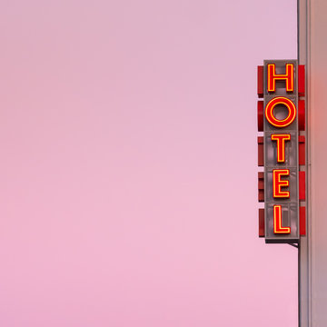 Neon hotel sign on the building corner with pink sunset sky at background.