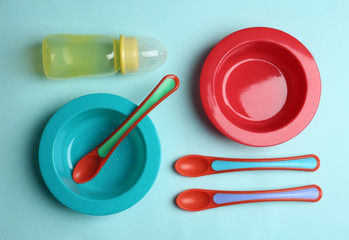 Poster Pays d Asie Set of colorful plastic dishware on light blue background, flat lay. Serving baby food