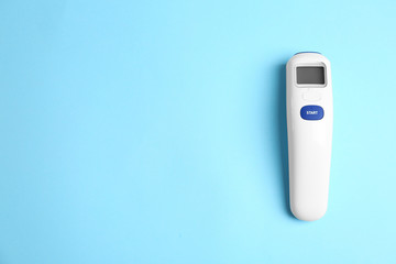 Modern non-contact infrared thermometer on light blue background, top view. Space for text