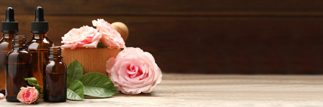 Bottles of rose essential oil and flowers on wooden table, space for text. Banner design