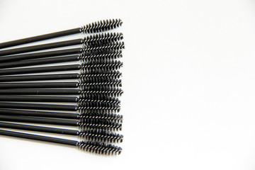 makeup artist set, lots of black mascara brushes on a white background close-up