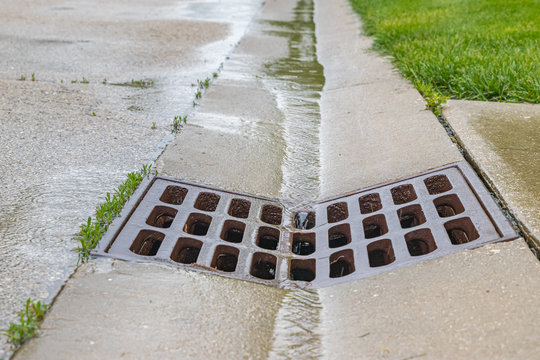 Closeup of rain water running down street gutter and flowing into storm sewer system drainage grate