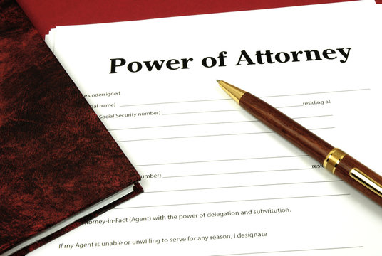 Power of Attorney Form ready to sign with book and pen.