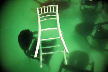 High Angle View Of Wooden Chairs In Water