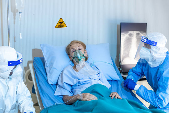 Doctor and psychologist working with female old patient during taking oxygen mask to stimulate breathing system. Old patient gets mental support from psychologist while taking medical treatment on bed