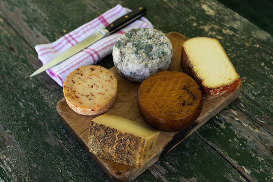 Top view of a table of assorted cheeses (blue cheese, smoked cheese ...) on a rustic table with a knife