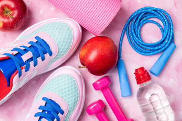 Yoga mat, sport shoes, jumping rope, dumbbells, apple, bottle of water on pink background. Concept...