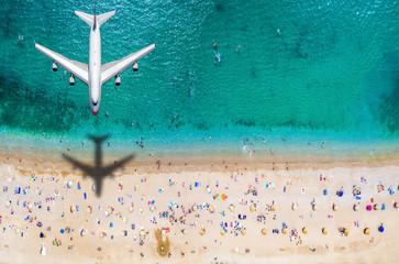 Papiers peints Montagne Sommer Reisekonzept mit einem Flugzeug welches über einen vollen Strand mit Menschen und türkisem Meer fliegt