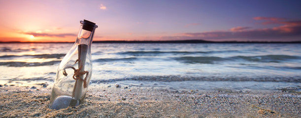romantic sunset at the beach with bottle with a message