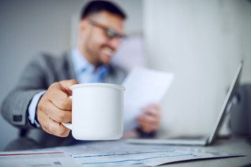 Beautiful caucasian classy smiling businessman in suit and with eyeglasses holding in one hand coffee and in other document and looking at it. Selective focus on mug with coffee. Office interior.