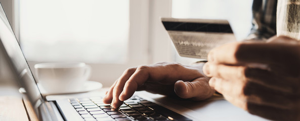 Man hand holding credit card and using laptop at home, Businessman or entrepreneur working, Online shopping, e-commerce, internet banking, spending money, working from home concept - fototapety na wymiar
