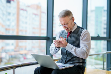 Thoughtful middle aged businessman in suit with a laptop. Man sitting near the window working with...
