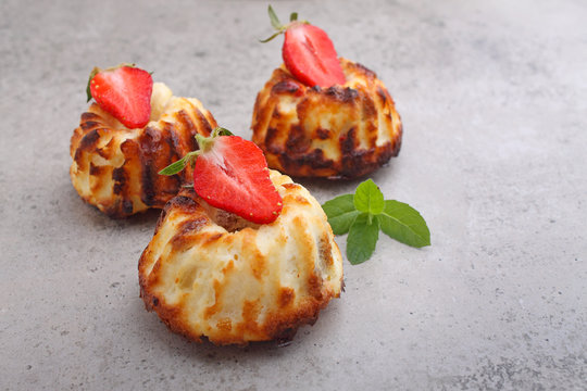 Cottage cheese casserole decorated with mint and strawberry on a concrete background.