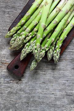Banches of fresh green asparagus on a wooden background, top view