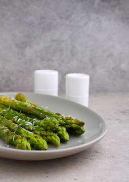Grilled fresh asparagus with parmesan in a plate on a concrete background
