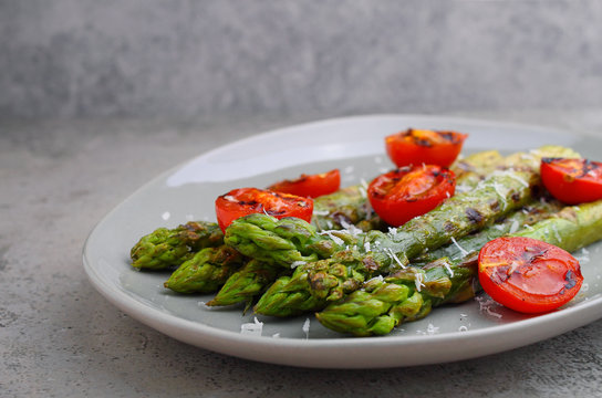 Grilled fresh asparagus with parmesan and tomatos in a plate on a concrete background