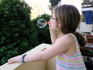 Funny lovely girl blowing soap bubbles from the balcony